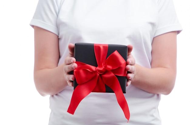 Kobiece ręce trzymając pudełko z czerwoną kokardą