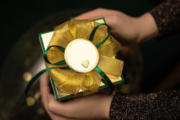 Kobiece ręce trzymając pudełko zawinięte w zielony papier ze złotą kokardą.