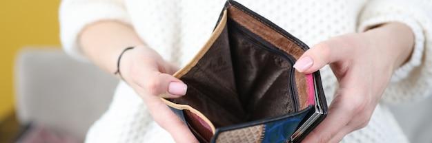 Kobiece ręce trzymając pusty skórzany portfel zbliżenie koncepcji kryzysu gospodarczego