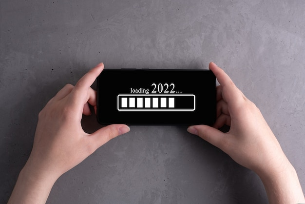Kobiece ręce trzymając smartfon wyświetlono poziom ładowania 2022 na szarym tle betonu, koncepcja nowego roku, zbliżenie.