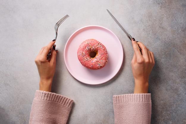 Kobiece ręce trzymając widelec i nóż cięcia pączek na różowy talerz na tle kamienia.