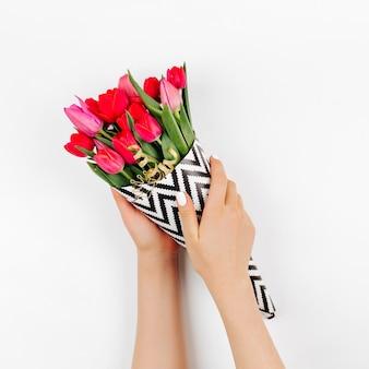 Kobiece ręce trzymające bukiet tulipanów zawinięty w papier