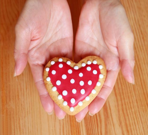 Kobiece ręce trzymające ciasteczka w kształcie serca z ostrożnością