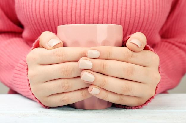 Kobiece ręce trzymające filiżankę kawy na drewnianym stole z bliska