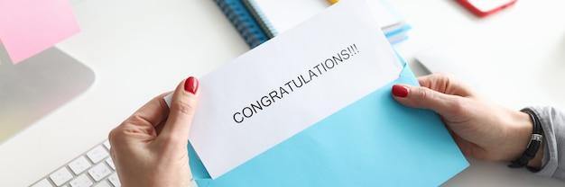 Kobiece ręce trzymające kopertę z gratulacjami zbliżenie