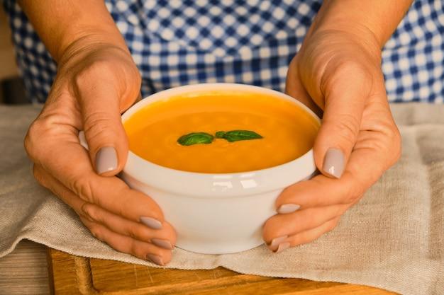 Kobiece ręce trzymające miskę gorącej zupy dyniowej podawanej z zieloną bazylią