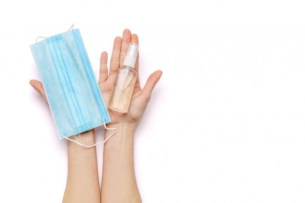 Kobiece ręce trzymające mydło w płynie lub dozownik sprayu odkażającego do rąk i medyczną maskę ochronną na białej ścianie ze ścieżką przycinającą.