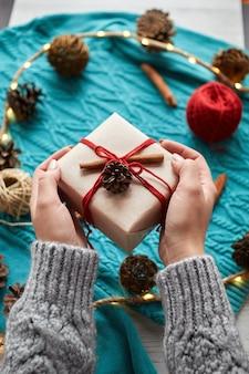 Kobiece ręce trzymające pudełko na prezent świąteczny na tle czerwonych skarpet, niebieski sweter z dzianiny i girlandę ze stożkami. przekazuje prezent
