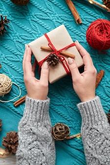 Kobiece ręce trzymające pudełko na prezent świąteczny na tle czerwonych skarpet, niebieski sweter z dzianiny i girlandę ze stożkami
