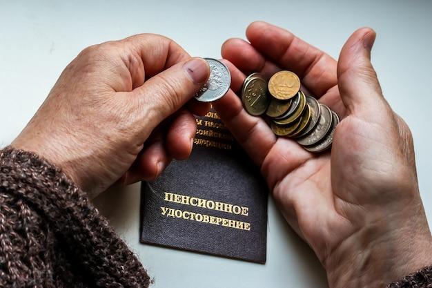 Kobiece ręce trzymające rosyjskie monety nad świadectwem emerytalnym