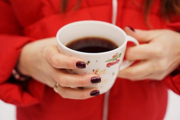 Kobiece ręce trzymające świąteczny kubek z gorącym ciemnym napojem na zewnątrz w zimowy dzień