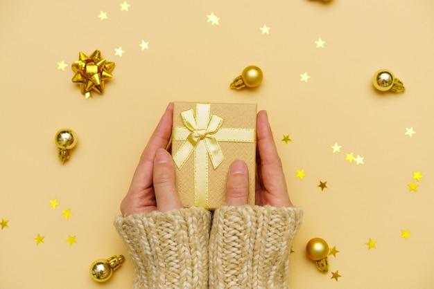 Kobiece ręce trzymające wesołe świąteczne pudełko na żółtym ozdobionym świątecznym tle kobieta przygotowująca...