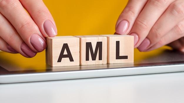 Kobiece ręce układają drewniane klocki z literami aml na czarnej powierzchni notatnika. aml skrót od anti-money laundering, koncepcja biznesowa, żółte tło, selektywne skupienie
