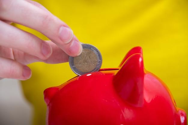 Kobiece ręce umieścić monetę w gnieździe czerwonej skarbonki, zbliżenie. koncepcja oszczędzania.