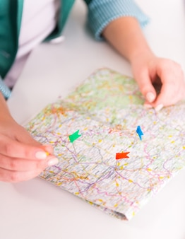 Kobiece ręce umieszczają flagi na mapie.