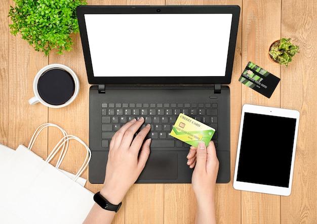 Kobiece ręce używać laptopa i karty kredytowej. widok z góry