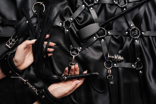 Kobiece ręce w kajdankach na ciemnym jedwabnym prześcieradle z batem