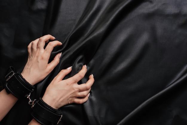 Kobiece ręce w kajdankach na ciemnym jedwabnym prześcieradle