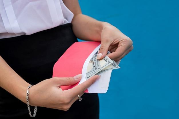 Kobiece ręce w kajdankach trzymając kopertę z dolarami. pojęcie korupcji i przekupstwa