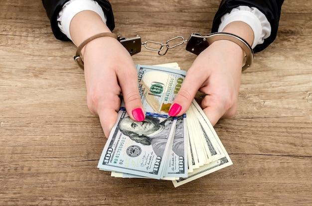 Kobiece ręce w kajdankach z dolarami w rękach