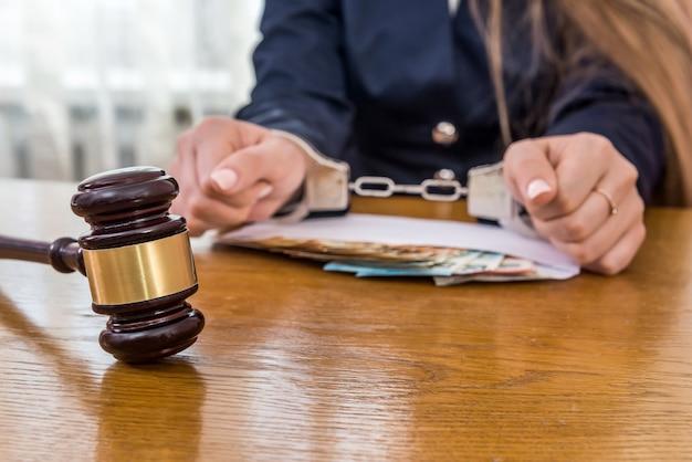 Kobiece ręce w kajdankach z pieniędzmi i młotkiem sędziego