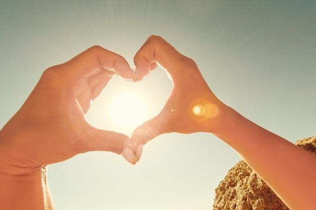 Kobiece ręce w kształcie serca na tle nieba przechodzą promienie słoneczne.