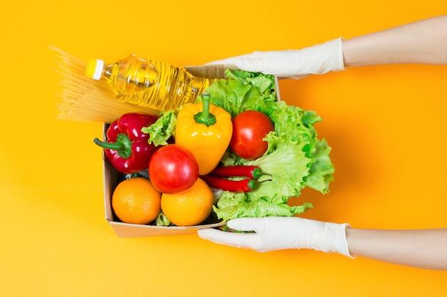 Kobiece ręce w rękawiczkach medycznych trzymają kartonowe pudełko z jedzeniem, olejem słonecznikowym, pieprzem, chili, pomarańczami, pomidorami, makaronem, odizolowane na pomarańczowym