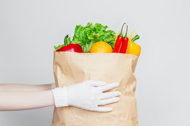 Kobiece ręce w rękawiczkach medycznych trzymają papierową torbę z jedzeniem, warzywami, pieprzem, chili, świeżymi ziołami na białym tle, bezpieczną dostawą żywności