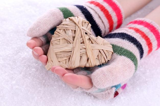 Kobiece ręce w rękawiczkach z sercem na śniegu
