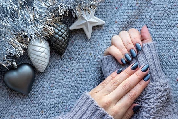 Kobiece ręce w sweter z niebieskimi błyszczącymi paznokciami