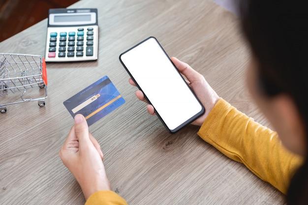 Kobiece ręce w żółtej koszuli trzymające telefon komórkowy z pustym ekranem i kartą kredytową na biurku oraz korzystające z telefonu komórkowego do zakupów online, bankowości internetowej, handlu online