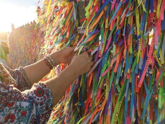 Kobiece ręce wiązanie kolorowych wstążek na siatce kościoła bonfim w salvador bahia w brazylii.