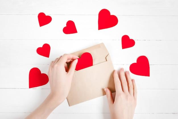 Kobiece ręce wkładają czerwone serca do gratulacyjnej koperty na białym drewnie