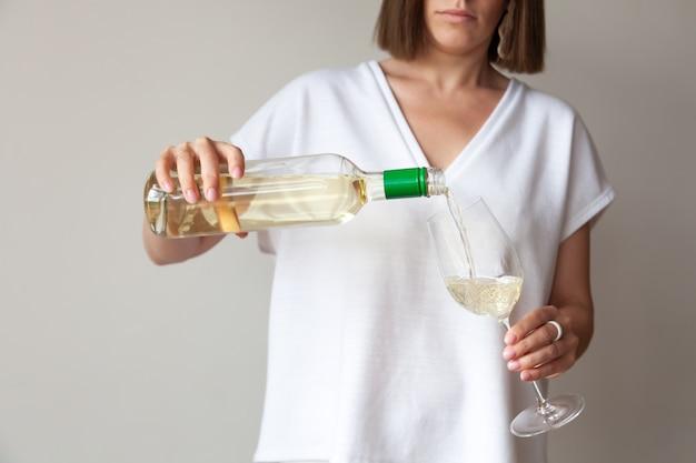 Kobiece ręce wlewają białe wino z butelki do szkła