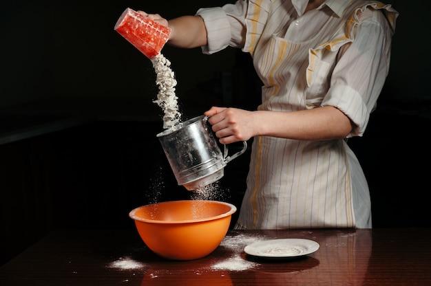 Kobiece ręce wlewając mąkę do stalowego przesiewacza