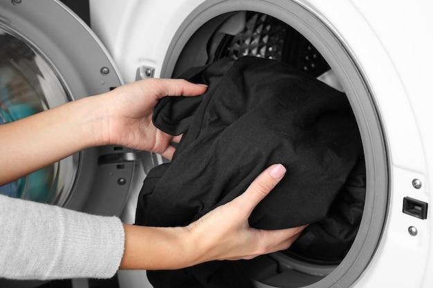 Kobiece ręce wychodzi czyste ubrania z pralki