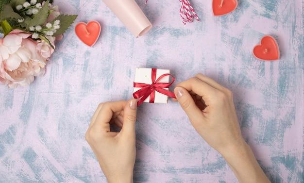 Kobiece ręce wyciągają czerwoną wstążkę na pudełku na jasnym tle. życzenia świąteczne i noworoczne lub sezonowe. selektywna ostrość