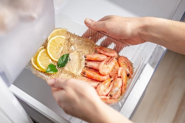 Kobiece ręce wyciągają z lodówki plastikowy pojemnik z ryżem, krewetkami i cytryną