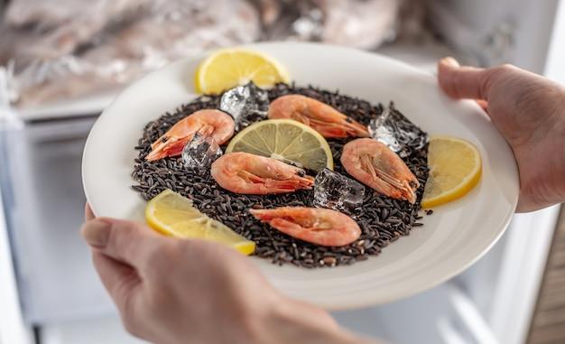 Kobiece ręce wyciągają z lodówki talerz czarnego ryżu, krewetek i cytryny