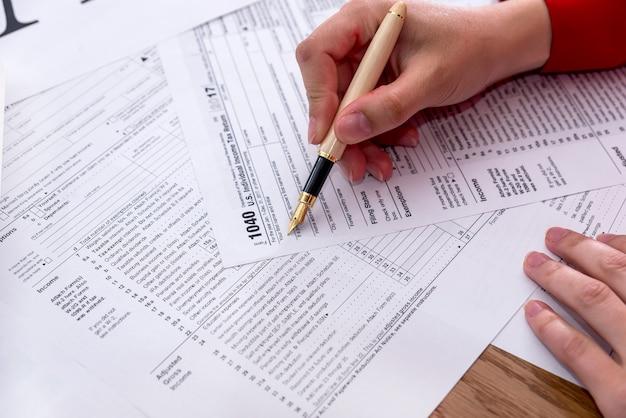 Kobiece ręce wypełniające formularz 1040 z bliska