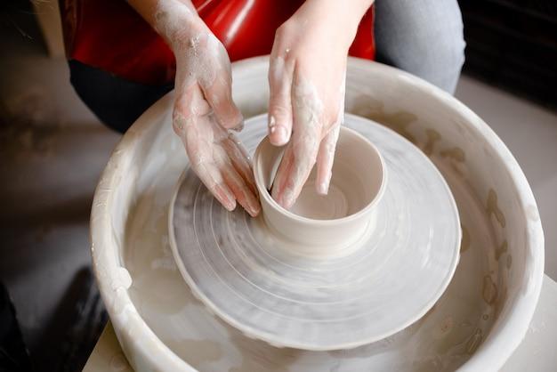 Kobiece ręce, wytwarzając ceramiczny kubek na kole garncarskim.