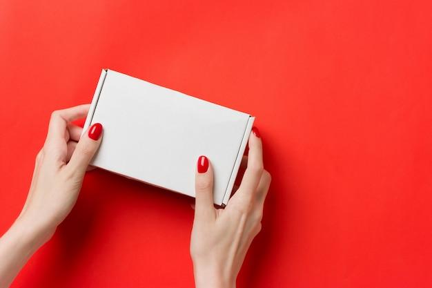 Kobiece ręce z białym pudełku na czerwonym tle