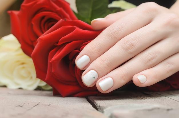 Kobiece ręce z białym wzorem paznokci gospodarstwa czerwona róża