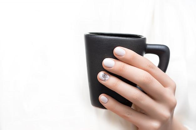 Kobiece ręce z białym wzorem paznokci trzymając czarny kubek.
