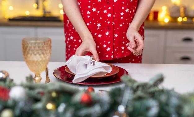 Kobiece ręce z bliska nakryć stół na boże narodzenie