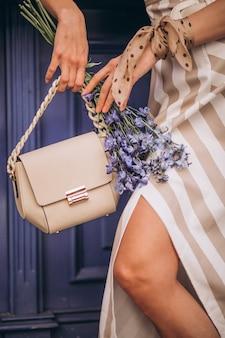 Kobiece ręce z bliska trzymając torbę i kwiaty