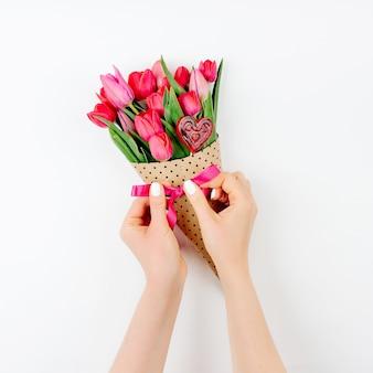 Kobiece ręce z bukietem tulipanów. piękne wiosenne różowe kwiaty.