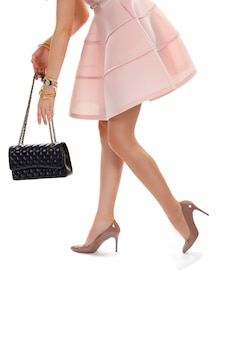 Kobiece ręce z czarną torebką. buty na obcasie i lekka sukienka. ciemna torba z paskiem na łańcuszek. błyszczące obuwie i zegarek na rękę.