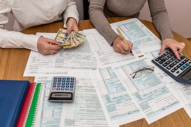Kobiece ręce z dolarami i innymi wypełnieniami formularza 1040
