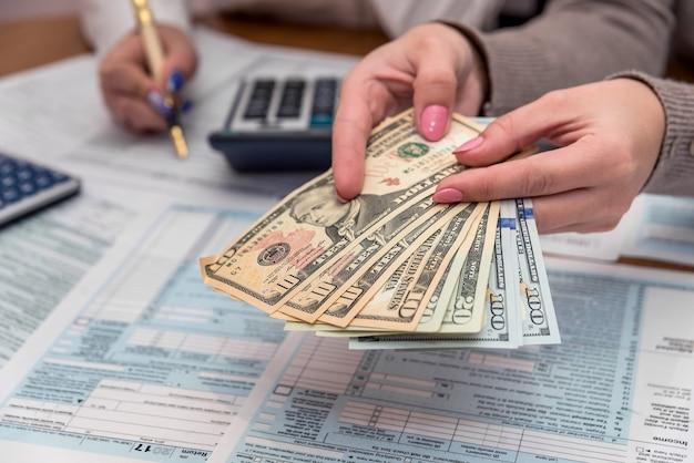 Kobiece ręce z formularza podatkowego dolara i 1040